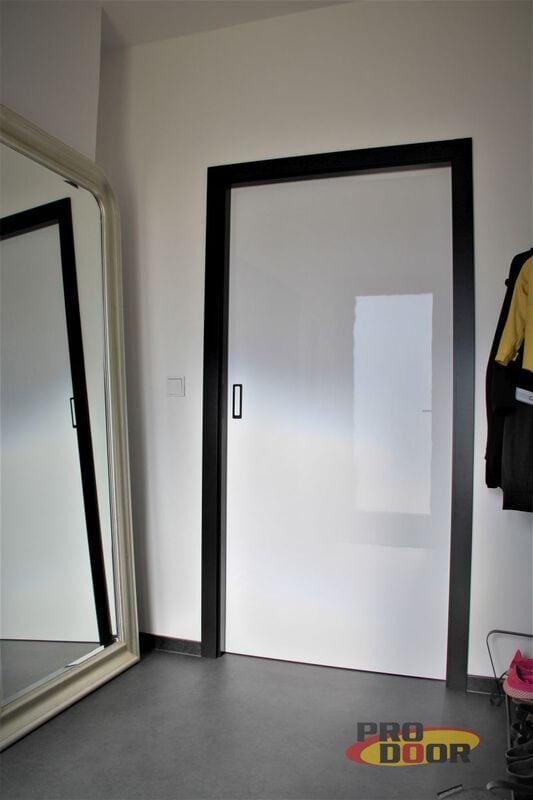 leské bílé posuvné dveře do pouzdra černá zárubeň a kování